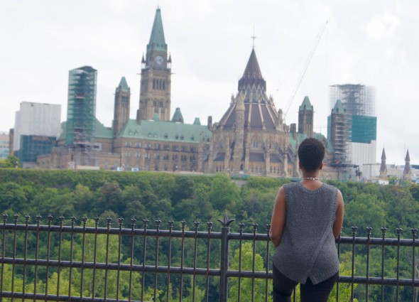 Woman stands in front of Parlimentary building in Ottawa